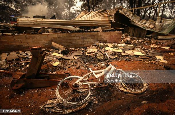 A burnt bicycle lies on the ground in front of a house recently destroyed by bushfires on the outskirts of the town of Bargo on December 21 2019 in...