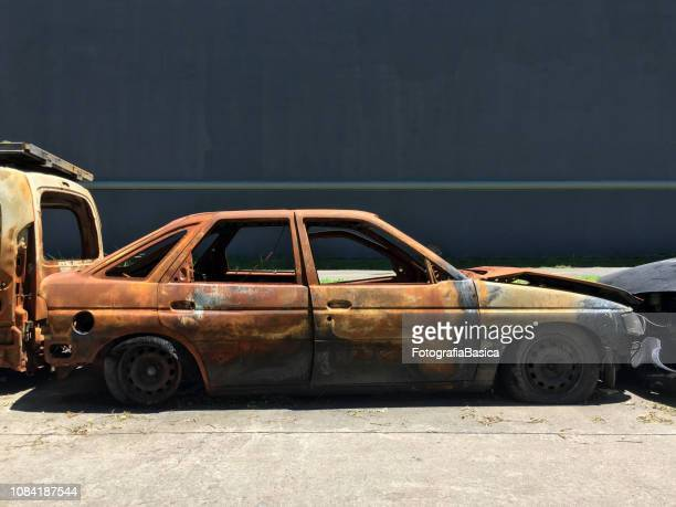 burnt car in the street - car crash wall stock photos and pictures