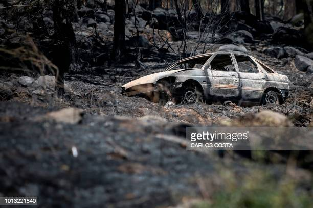 Burnt car is pictured near Monchique, in Algarve, on August 8, 2018. - Wildfires scorched a path towards more villages in Portugal's southern Algarve...