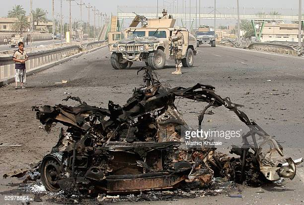 A burnt car lies in a road as US soldiers secure the scene of a suicide car bomb explosion which failed to hit a US military convoy May 25 2005 in...