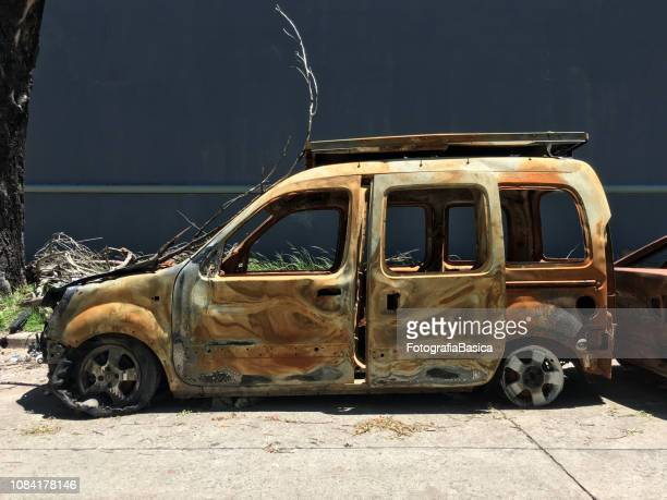 burnt car next to sidewalk - car crash wall stock photos and pictures