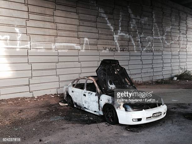 burnt car on field against wall - car crash wall stock photos and pictures