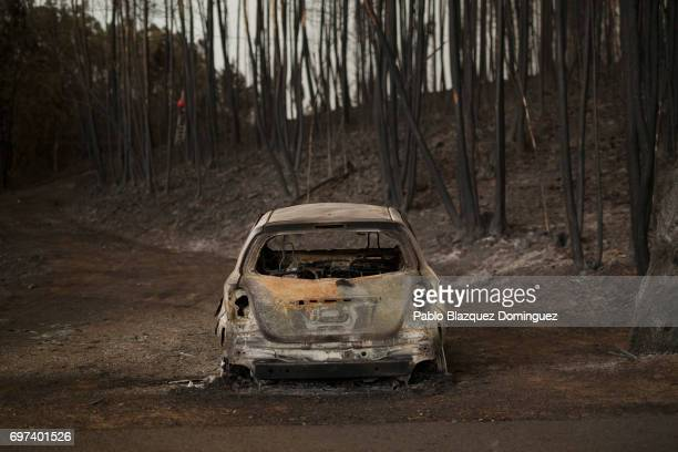A burnt car stand next to a forest after a wildfire took dozens of lives on June 18 2017 near Castanheira de Pera in Leiria district Portugal On...