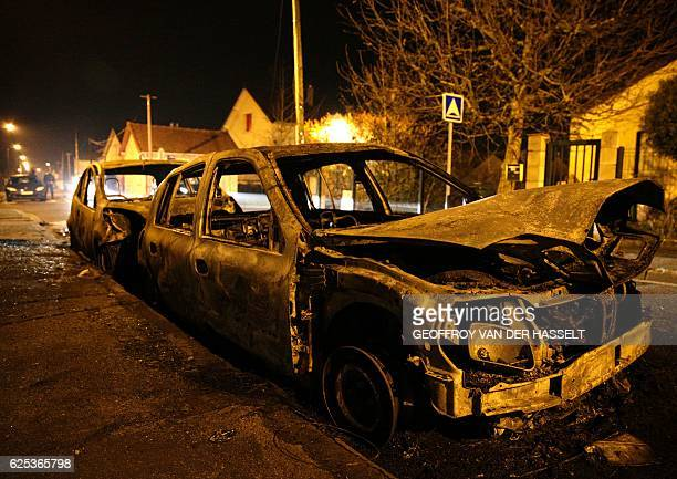 Burnt cars are seen on the street after protesters clashed with police in BeaumontsurOise north of Paris early on November 24 2016 The protests...