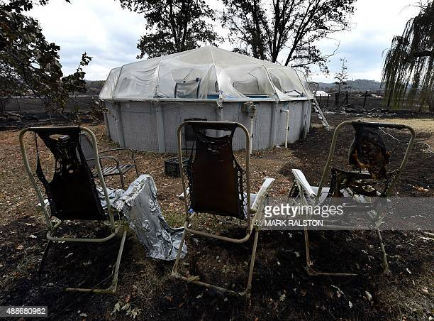 Burnt chairs stand in front of a swimming pool beside a fire destroyed house after the Valley Fire swept through the town of Middletown California on...