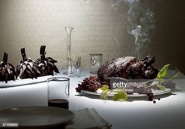 burnt chicken & artichokes on a nice dining table - burnt stock pictures, royalty-free photos & images