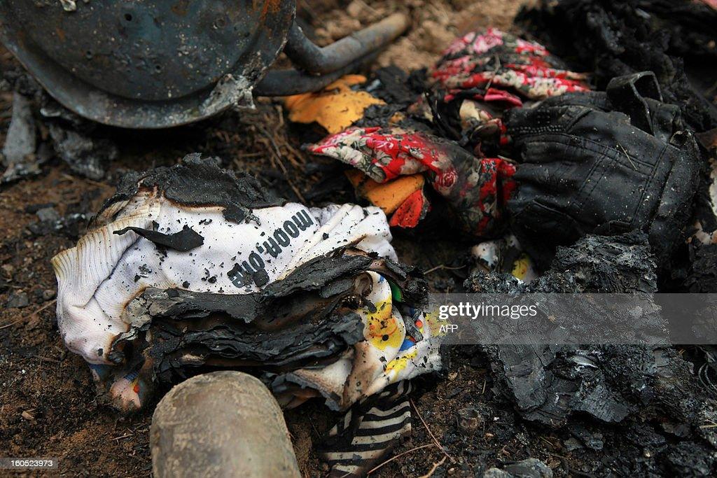 Burnt clothes lie on the ground after a bus plunged off a road and down a hill, catching fire after the impact, in Ningxian, northwest China's Gansu province on February 2, 2013. The accident took the lives of 18 people. CHINA