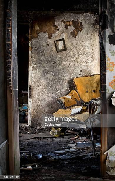 Verbrannt, beschädigte Einrichtung von zu Hause mit zerstört Stuhl und Bücher