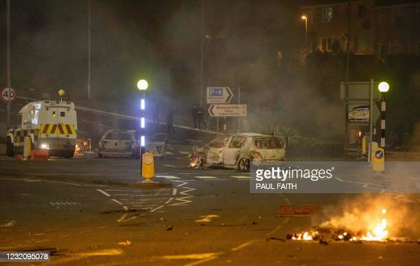Burnt out car and flames are seen at the scene of violence in Newtownabbey, north of Belfast, in Northern Ireland on April 3, 2021. - The disturbance...