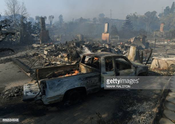 A burnt out car and house is seen during the Thomas wildfire in Ventura California on December 5 2017 Firefighters battled a windwhipped brush fire...