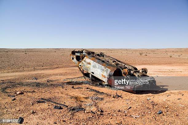 a burnt out car in a desert - abandoned car stock photos and pictures