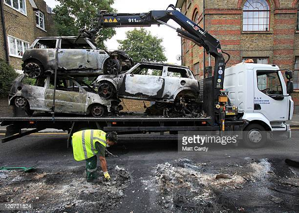 Burnt out cars are removed from a residential street in Hackney on August 9 2011 in London England Emergency services have been cleaning up after a...