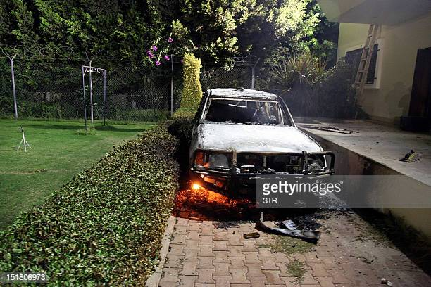 A burnt out vehicle sits smoldering in flames after it was set on fire inside the US consulate compound in Benghazi late on September 11 2012 An...