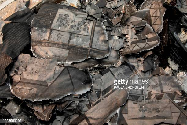 Burnt photos from yearbook are seen as Fred Skaff and his son Thomas clear debris from their home destroyed by the Almeda Fire, on September 16, 2020...