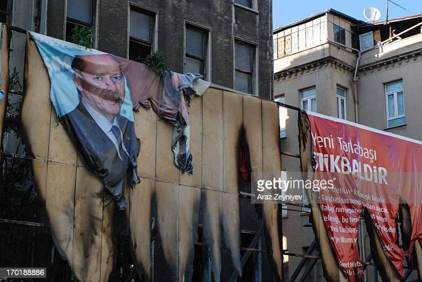 Burnt poster of the Prime Minister of Turkey, Recep Tayyip Erdogan, advertising city redevelopment of the poor Tarlabashi district which is very...