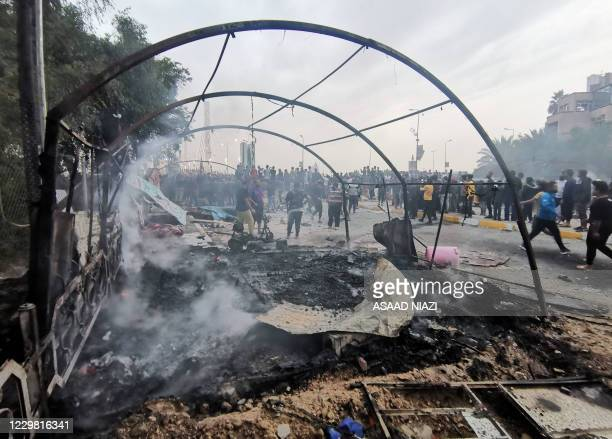 Burnt strucure fumes amid clashes between Iraqi anti-government protesters and supporters of firebrand Shiite cleric Moqtada Sadr, in the southern...