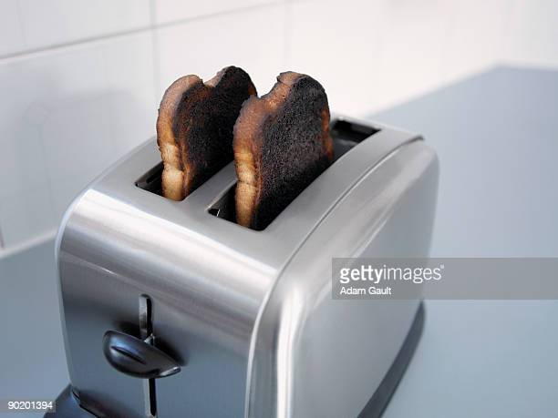 burnt toast in toaster - burnt stock pictures, royalty-free photos & images