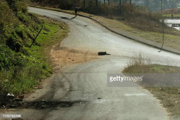 Burnt tyres and broken glass lie on a road close to the centre of Mbabane on July 3, 2021 as a tense calm returns to Eswatini after days of violent...