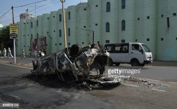 Burnt vehicle is seen near the 'Dera Sacha Sauda' ashram of controversial Indian guru Ram Rahim Singh in Sirsa on August 27, 2017. Supporters of an...