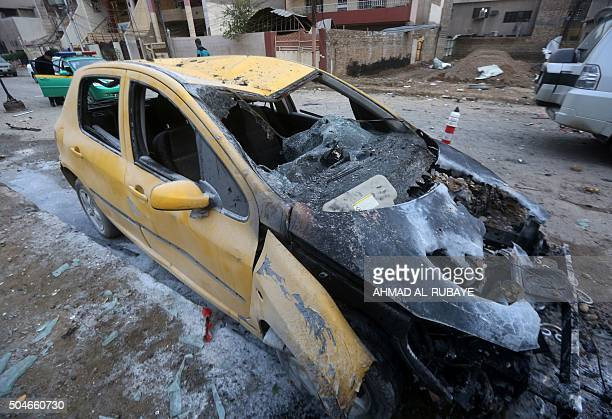 A burntout car is seen in the street in eastern Baghdad the day after a bomb attack on January 12 2016 Jihadist gunmen and bombers killed at least 12...