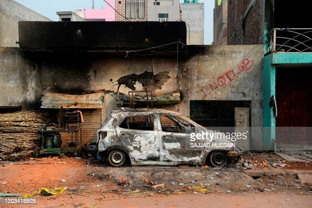 Burnt-out vehicle is pictured following clashes between people supporting and opposing a contentious amendment to India's citizenship law, in New...