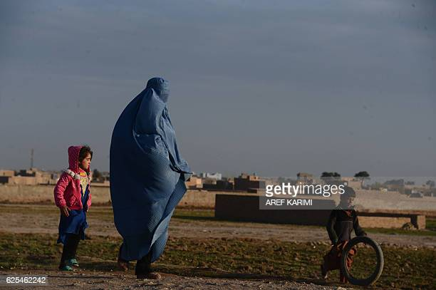 A burqa clad Afghan woman with her children walks on the outskirts of Herat on November 24 2016 / AFP / AREF KARIMI