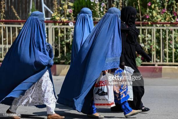 Burqa clad Afghan women walk near the premises of Wazir Akbar Khan hospital in Kabul on September 1, 2021.