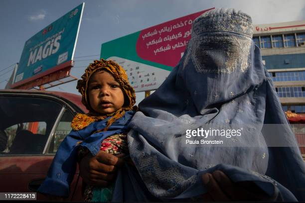 Burqa clad beggar moves through Kabul traffic hoping to make some small money from people driving by on September 29, 2019 in Kabul, Afghanistan. The...