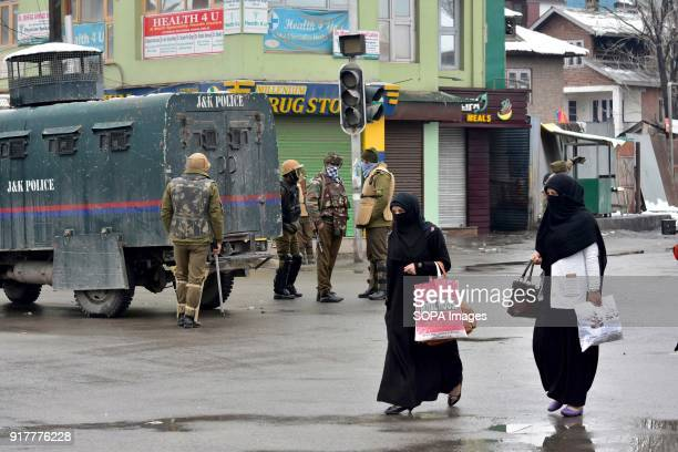 Burqa clad Kashmiri women walk past Indian paramilitary troopers standing guard near the encounter site in Srinagar Indian administered Kashmir Two...