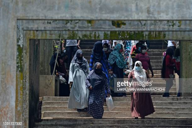 Burqa clad Muslim women climb down a flight of stairs at a zoological park on the outskirts of Colombo on March 14, 2021.