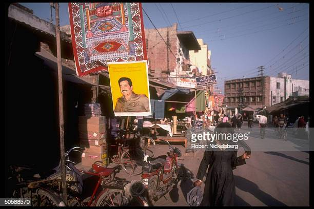 Burqa clad woman on shopping street passing Saddam Hussein portrait adorned storefront in gulf war proIraqi side Moslem community of Aligarh Uttar...