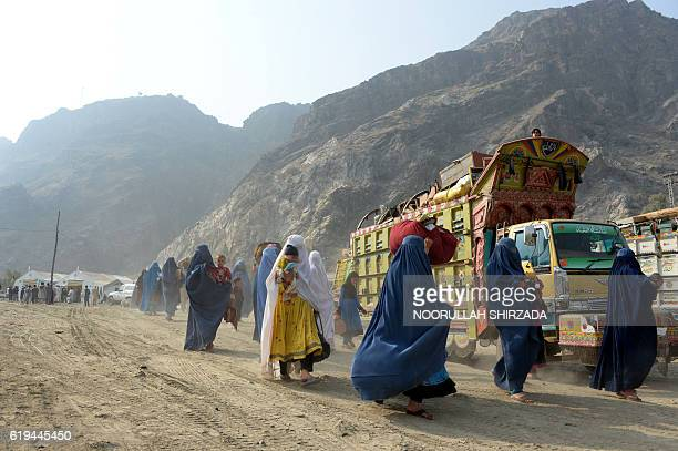 Burqaclad Afghan refugees arrive at the United Nations High Commissioner for Refugees repatriation center in Torkham as they cross through the main...