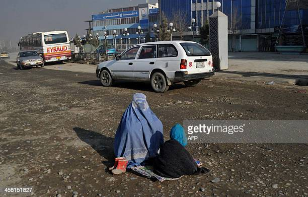 A burqaclad Afghan resident and her child beg for alms on a street in Kabul on December 20 2013Some nine million Afghans or 36 percent of the...