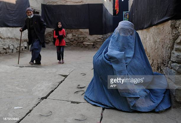 A burqaclad Afghan resident begs near the entrance to a Shiite mosque ahead of Ashura commemorations in Kabul on November 13 2013 Ashura mourns the...