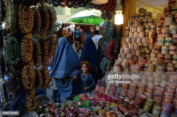 A burqaclad Afghan woman and child walk through a market ahead of Eid AlFitr festivities at a local market in Jalalabad on June 22 2017 Muslims...