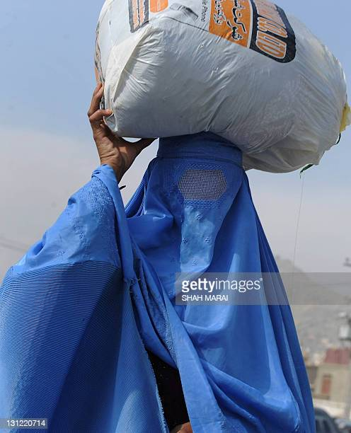 A burqaclad Afghan woman caries a bag over her head as she walks in the old section of Kabul on November 3 2011 Despite massive injections of foreign...