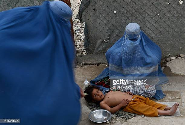 A burqaclad Afghan woman gives alms to another woman begging with her child at a roadside near the shrine of Hazrati Ali ahead of 'Nowruz' the...