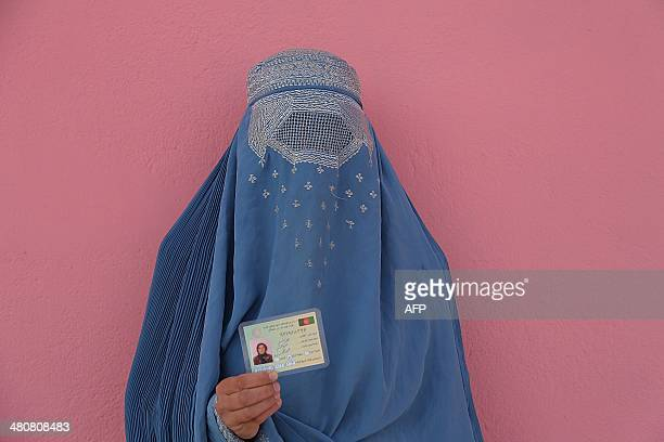 A burqaclad Afghan woman poses with her voter identification card at a registration center in Ghazni province on March 27 2014 Afghanistan's April 5...