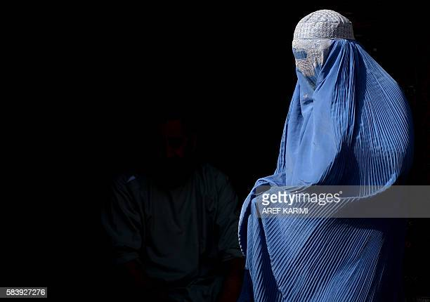 TOPSHOT A burqaclad Afghan woman walks along a road in Herat on July 28 2016 / AFP / AREF KARIMI