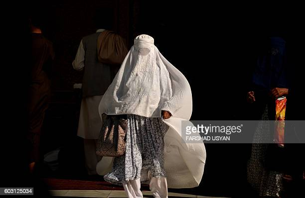 A burqaclad Afghan woman walks at the Hazrati Ali shrine in Mazari Sharif on September 12 2016 Afghans started celebrating Eid alAdha or 'Feast of...