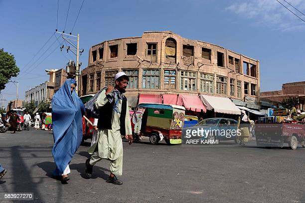 A burqaclad Afghan woman walks with a companion along a road in Herat on July 28 2016 / AFP / AREF KARIMI