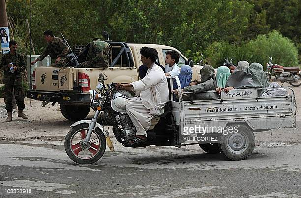 Burqaclad Afghan women commute on the back of a motorcycle truck in Kandahar's province Arghandab Valley on August 10 2010 NATO and the United States...