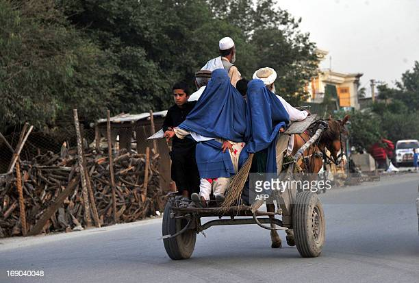 Burqaclad Afghan women ride on the back of a horsedriven cart in Jalalabad on May 18 2013 Some nine million Afghans or 36 percent of the population...