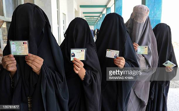 Burqaclad Afghan women show identification cards as they wait to cast their votes at a school converted to a polling centre in Kandahar on August 20...