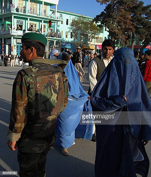 Burqaclad Afghan women walk past an Afghan National Army soldier on watch in front of the Hazrat Ali Shrine in the northern town of MazariSharif in...