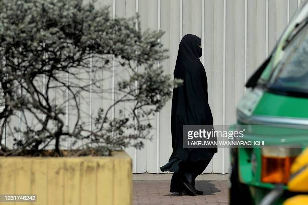 Burqa-clad Muslim woman walks along a road in Colombo on March 16, 2021. - The Sri Lankan government insisted March 16, that preventing Muslim women...