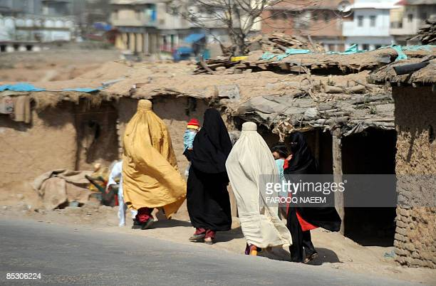 Burqaclad Pakistani woman walk by dwellings in a shanty inhabited by people from the country's North Western Frontier Province on the outskirts of...