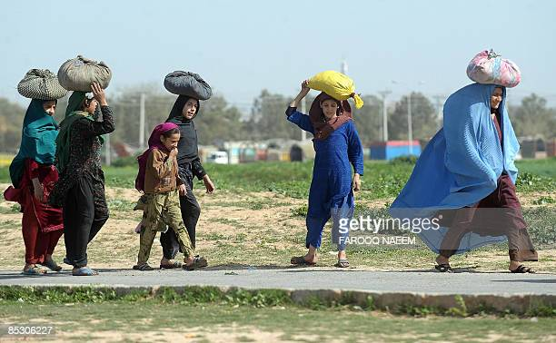 A burqaclad Pakistani woman walks with members of her family towards a shanty inhabited by people from the country's North Western Frontier Province...