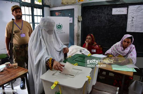 A burqaclad woman casts her vote during Pakistan's general election at a polling station during the general election in Pehawar on July 25 2018...