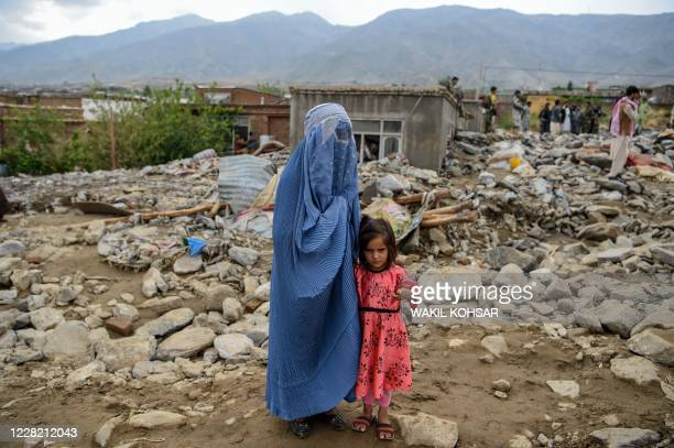 Burqa-clad woman stands near a young girl among households' debris after a flash flood affected the area at Sayrah-e-Hopiyan in Charikar, Parwan...